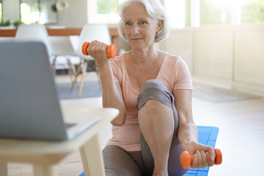 Senior woman doing fitness exercises at home through virtual class