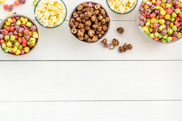 Colorful popcorn in bowl on white desk top-view copy space