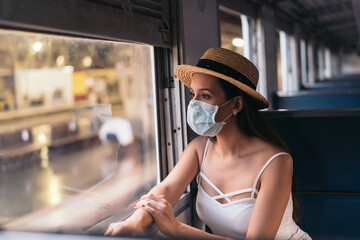 Young brunette woman traveling in Thailand on train during pandemic Coronavirus. 20s Hispanic in a...