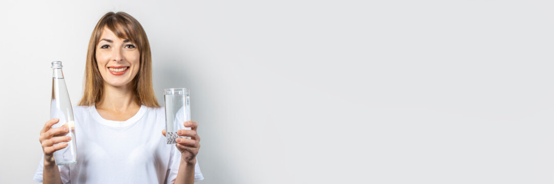 Young woman holds a bottle and a glass with clear water on a light background. Banner. Concept of thirst, heat, health and beauty care, water balance
