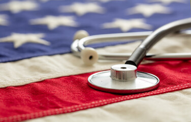 US health. Medical stethoscope on a USA flag, closeup view.