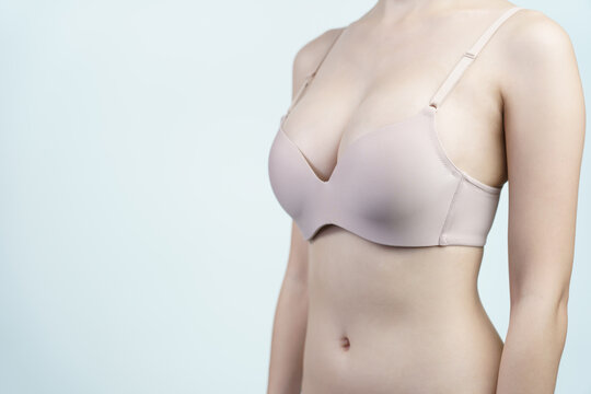 Woman wearing bra after breast augmentation plastic surgery with silicone breast implants.