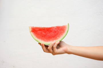 Hand holding a watermelon slice isolated on a white wall background.