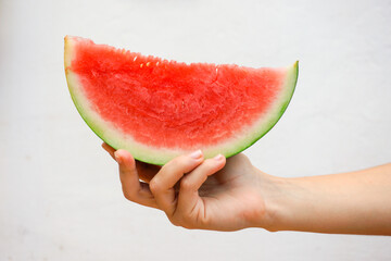 Hand holding a watermelon slice isolated on a white wall background. Close up view.