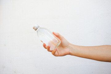 Hand holding a glass water bottle isolated on white. Hydration concept.