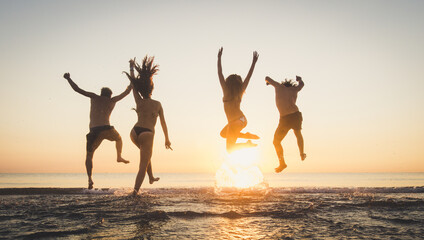 Group of happy friends running and jumping in the sea at sunset. Young people enjoy holiday...