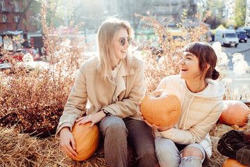 Girls holds pumpkins in hands on the background of the street.