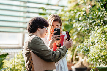 Young agricultural engineers taking photos on a smartphone in greenhouse