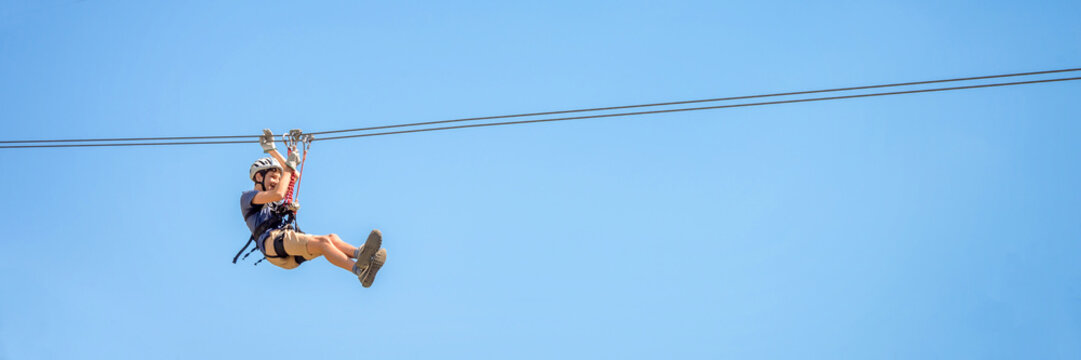 Teenager having fun on a zipline on panoramic blue sky background with copy space.