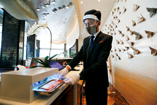 A receptionist staff wearing a face shield and a protective face mask uses an ultraviolet box to sterilise banknotes at The Margo Hotel, following the coronavirus disease (COVID-19) outbreak in Depok