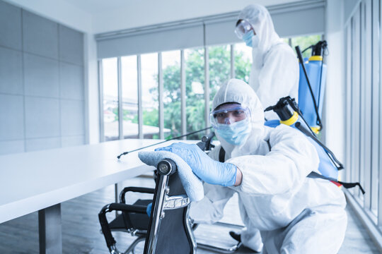 Specialist team in virus protective suite and mask spraying alcohol and cleaning covid19 infected area, Virus disinfection concept