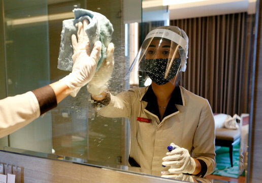 Staff wearing a face shield and a protective mask wipes a mirror at the room of The Margo Hotel, following the coronavirus disease (COVID-19) outbreak in Depok