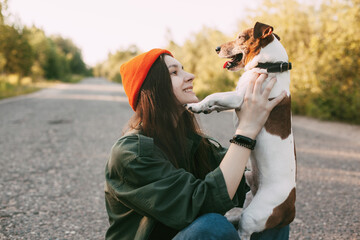 A pretty brunette holds her dog in her arms and smiles. The girl is resting with her pet in nature. The concept of friendship and care