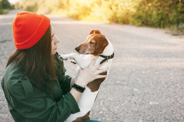 A beautiful girl in an orange hat holds her dog in her arms. The girl takes care of her pet and walks with him in the fresh air. Pet, friend, friendship, care