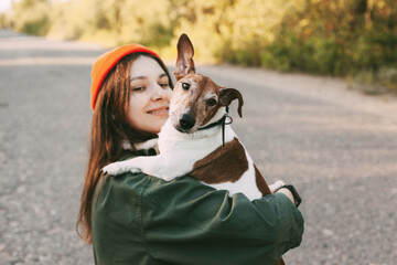 A pretty brunette holds her dog in her arms and smiles. The girl is resting with her pet in nature. The concept of friendship and care. Blurred background, space for text
