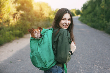 A smiling girl is holding a green backpack on her shoulder, from which a cute dog looks out. A girl and her friend travel together, take walks. The concept of friendship and care