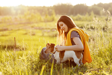 A beautiful young girl is sitting on the grass and hugging her dog. A girl and her pet are resting after a walk in nature. Friend, Friendship, Care. Space for text