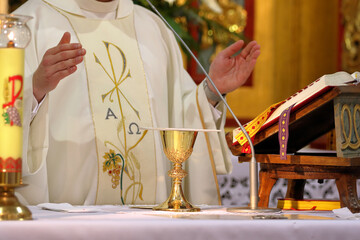 Chalice on the altar and priest celebrating mass in the background
