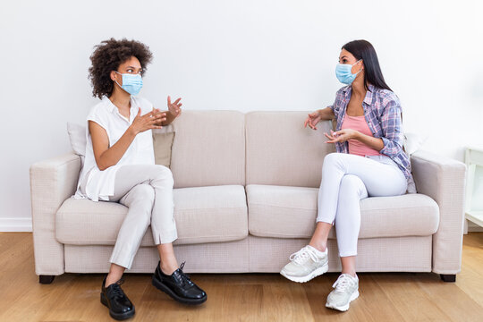 Two female best friends sitting in social distance wearing face mask and talking on the sofa, preventing covid 19 coronavirus pandemic infection spread.