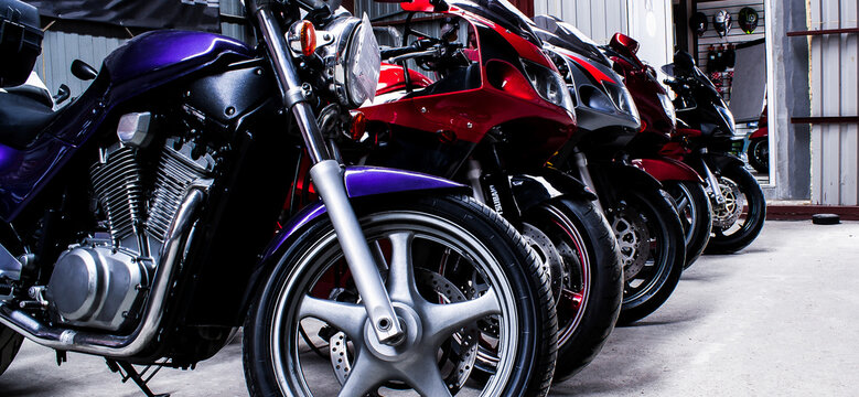 Colored sports, road beautiful bikes in a motor show, close up. Many motorcycles parked in a store. Sale of used cruise motorbikes in the cabin. Showroom equipment in the garage. Banner for web site