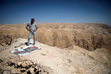 "Eitan Melet, a director at Israeli lobby ""Safeguarding Eternity"", stands next to a map near ruins of the ancient desert fortress of Cypros, near the Palestinian city of Jericho, in the Israeli-occupied West Bank"