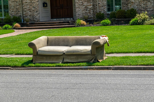 An old torn couch seen on the curb in front of a big house by an asphalt street waiting to be picked up by the trash department
