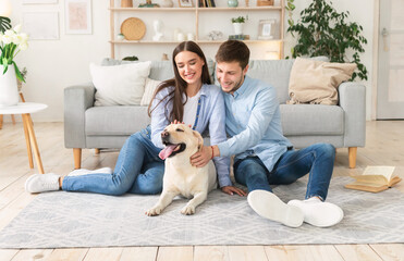 Young happy couple with dog sitting in living room