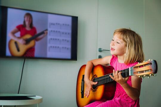 little girl having guitar lesson online at home