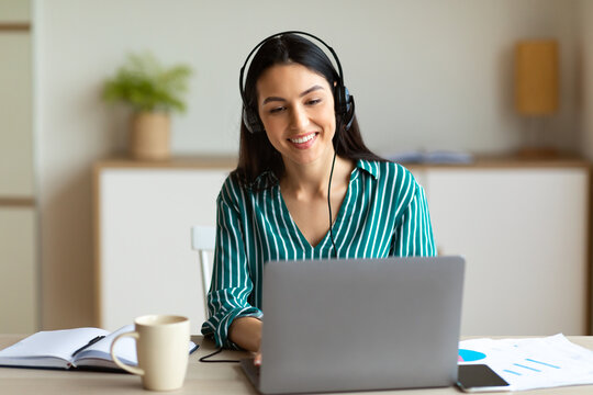 Woman In Headset Making Video Call Sitting At Laptop Indoor
