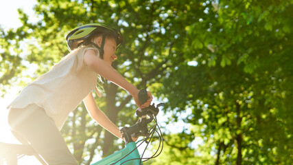 Happy teenager girl rides best bike on a summer sunny day in a city park. Against the background of...