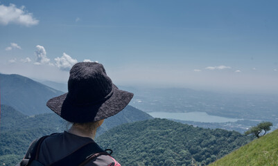 woman or girl looking the Landscape of Lake Como from an alpine trail.