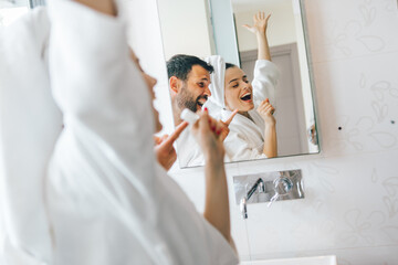 Young couple having fun and singing in bathroom