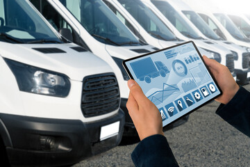 Manager with a digital tablet on the background of vans. Fleet management