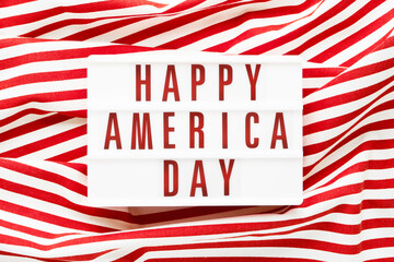 HAPPY AMERICA DAY written in light box on red background. Top view, copy space. Independence day...