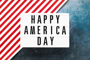 HAPPY AMERICA DAY written in light box on red-blue background. Top view, copy space. Independence...