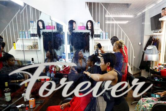 A hairdresser braids the hair of a client in a hair salon at the Matonge gallery in Brussels
