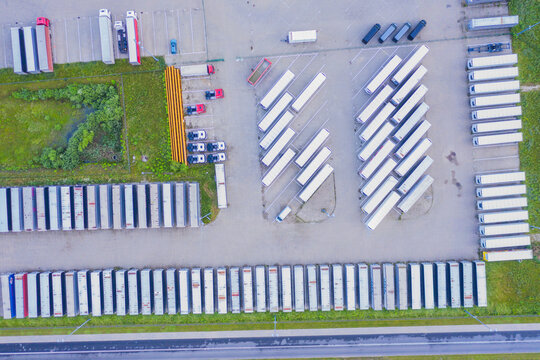 Aerial top view of white cargo trailer parking, trailer line up. Delivery, logistics.