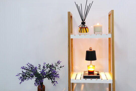 nice glass candle, aroma room reed diffuser and elelctric candle warmer are displayed in the white luxury bedroom