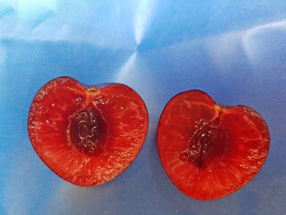 two heart shaped halfs of a cherry fruit