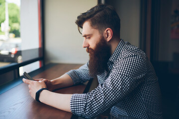 Side view of bearded young man dressed in casual t-shirt playing games on modern telephone...