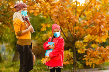 Mother and daughter wear face protection mask to protect himself from coronavirus covid 19. autumn