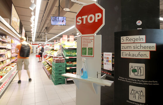 """A bottle of disinfection liquid and a sign saying """"5 rules for safe shopping"""" are displayed at a supermarket of Swiss retailer Denner in Glattbrugg"""