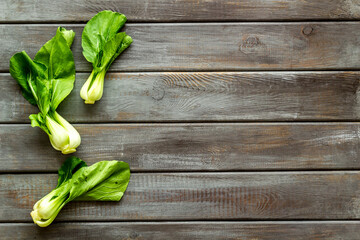 Bok choy harvest on wooden background top-down copy space