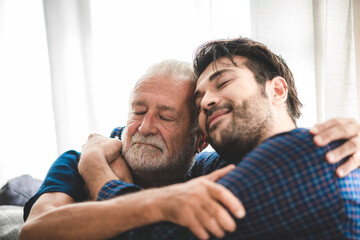 happy hipster adult son and senior father hugging at home, concept of stay at home with family