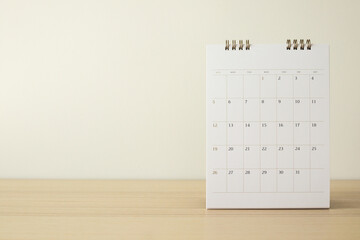 Calendar page close up on wood table with white wall background business planning appointment...