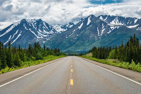 Road winding through the Alaskan wilderness in summer surrounded by mountains