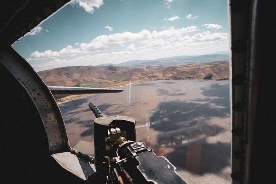 B-17 bomber plane from WWII flying above a deserted area on a sunny day