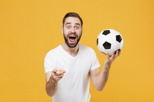 Shocked bearded man guy football fan in white t-shirt isolated on yellow background. People sport family leisure concept. Cheer up support favorite team with soccer ball point index finger on camera.