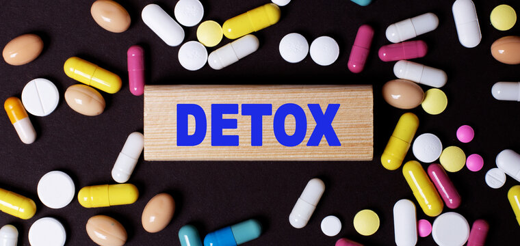 The word DETOX is written on a wooden block among multi-colored tablets on a dark background. Medical concept.
