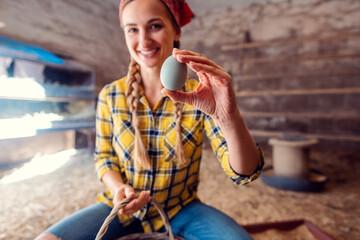 Farmer woman showing egg in a henhouse